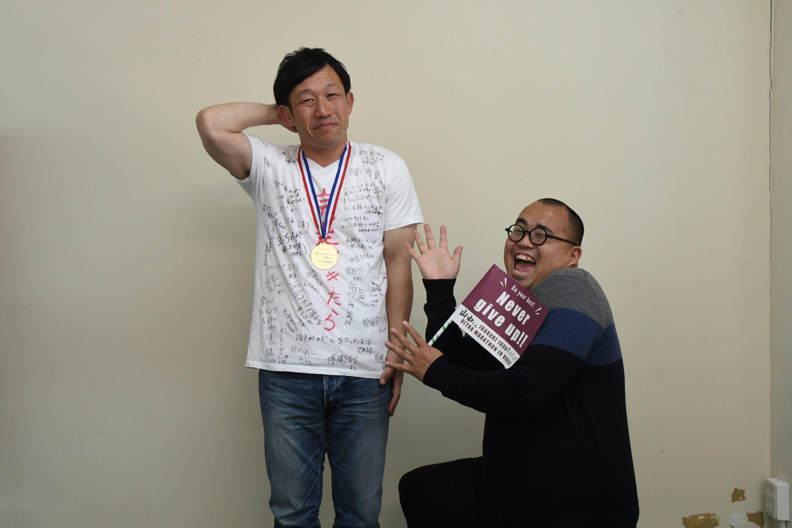 山中さんをたたえるでれすけさん(写真右)と、苦笑いする山中さん