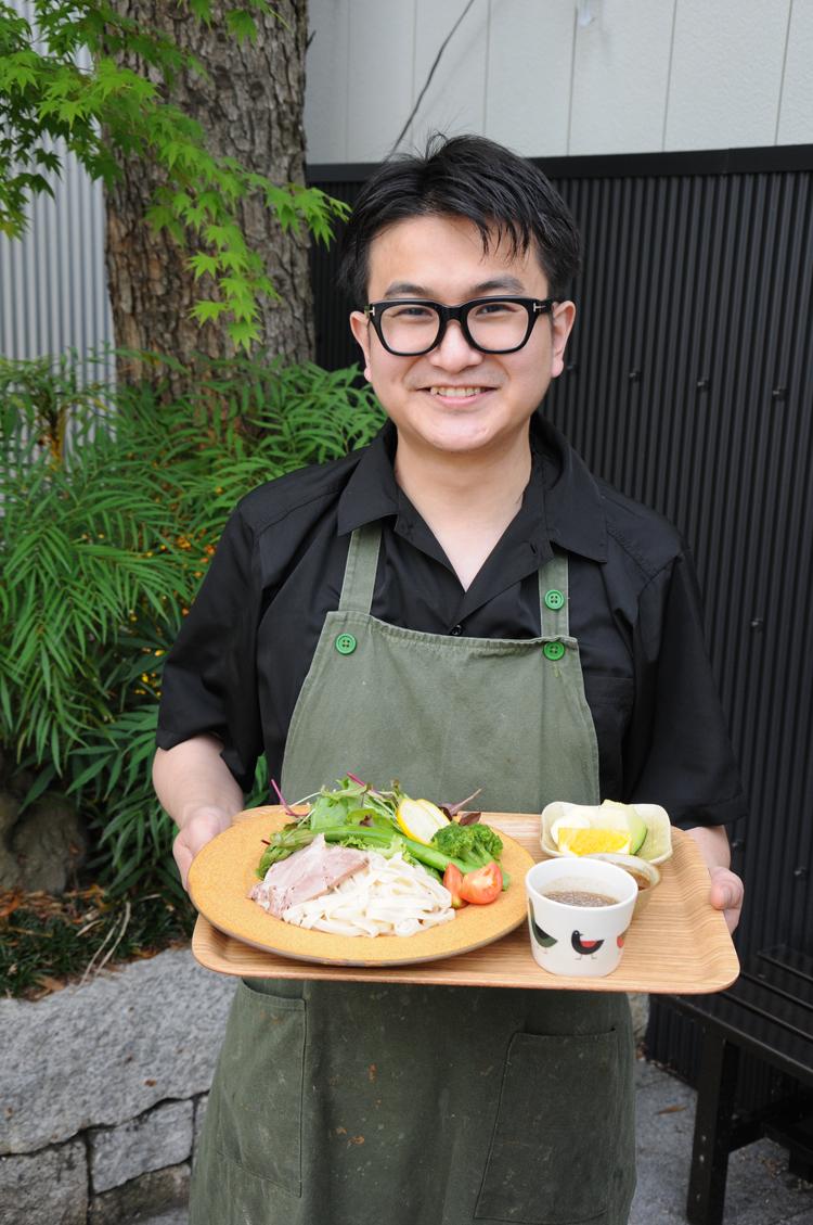 「かさまベジつけ麺」を持つ富田さん