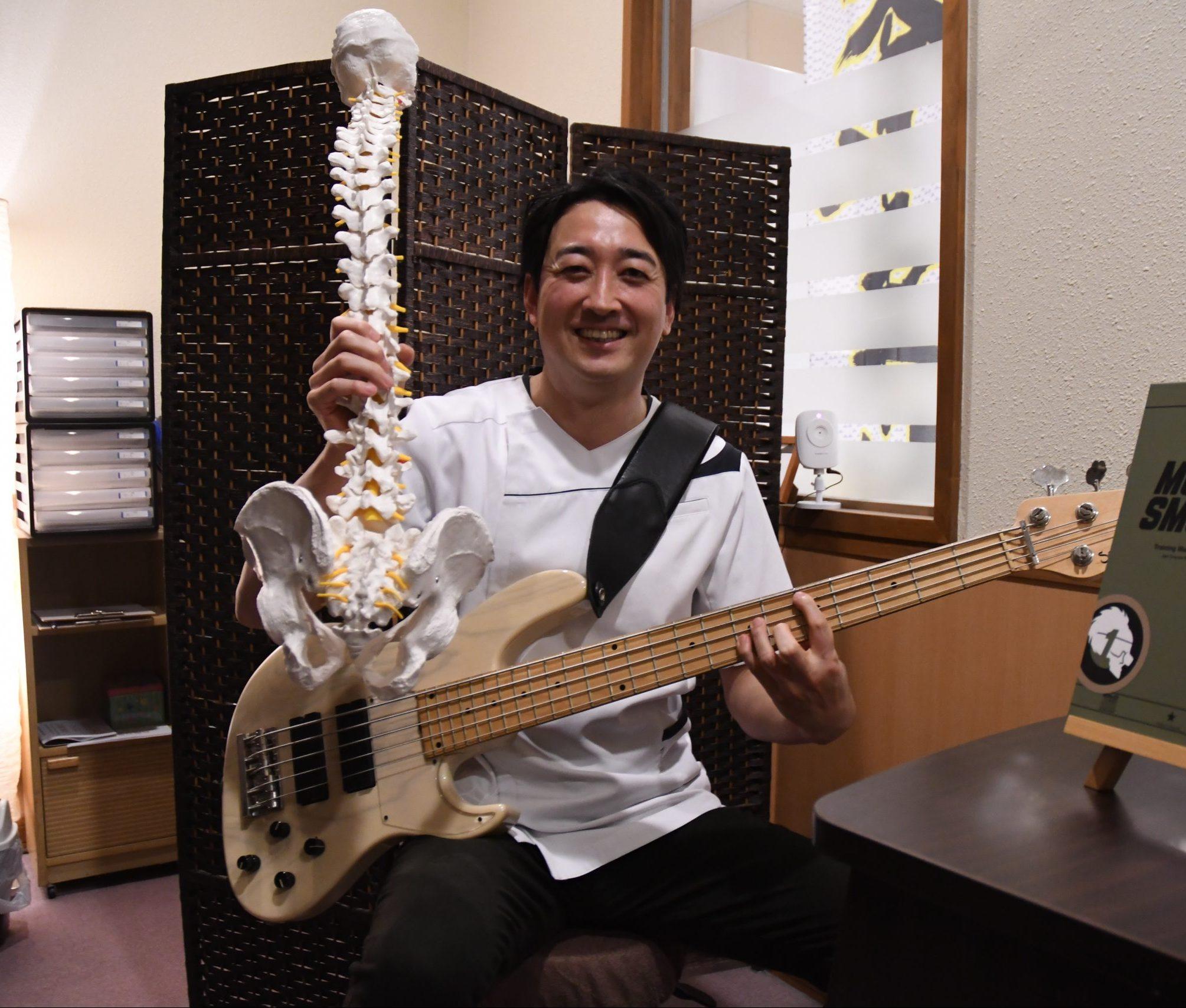 ベースギターと脊椎模型を持つ君和田さん