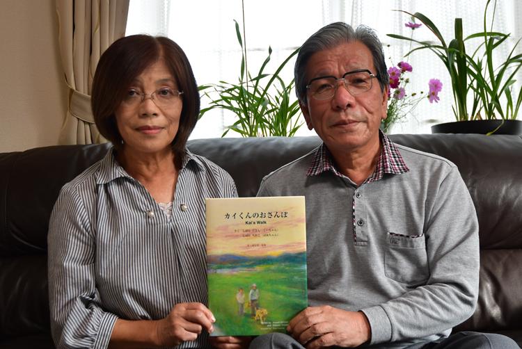 絵本「カイくんのおさんぽ」を持つ柴田さん夫婦