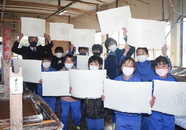 完成した台紙を掲げる児童たち