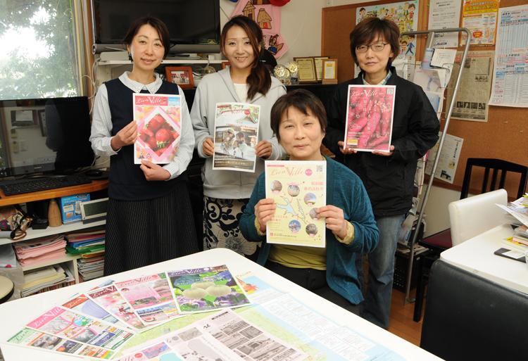 20号を持つ横田さんと、編集室のメンバー