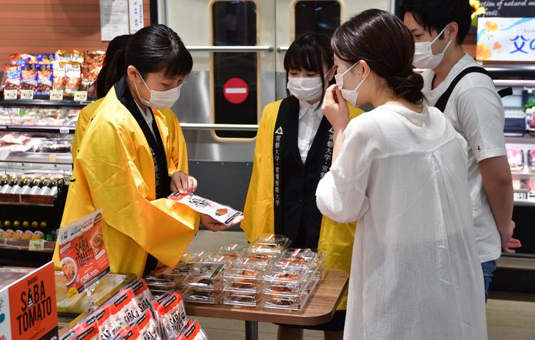 客に商品の説明をする学生