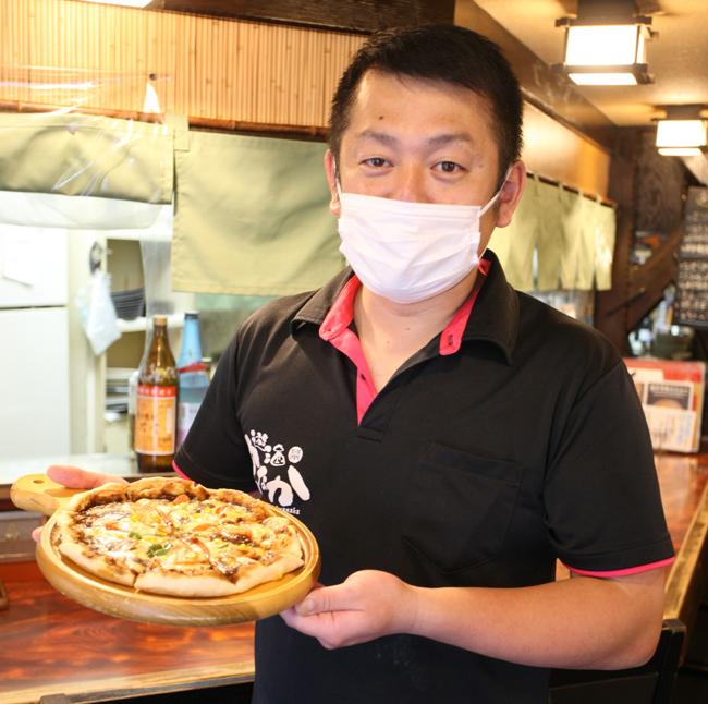 「西シェフコラボカレーピザ」を持つ店員