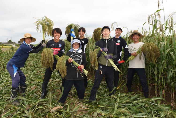 収穫した穂を持つ参加者
